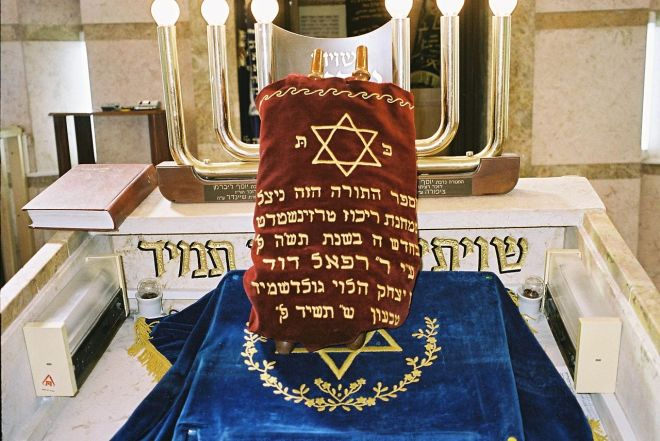 The Sefer Torah (Image Source: Wiki Commons - https://upload.wikimedia.org/wikipedia/commons/thumb/0/09/PikiWiki_Israel_4204_Sefer_Torah_from_Theresienstadt_concentration_camp.jpg/1280px-PikiWiki_Israel_4204_Sefer_Torah_from_Theresienstadt_concentration_camp.jpg)